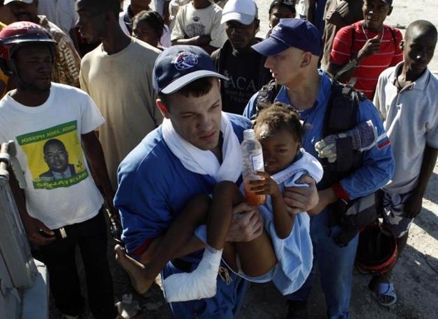 Soccorritori russi dopo aver salvato dalle macerie Olan Remi, 9 anni (Reuters)