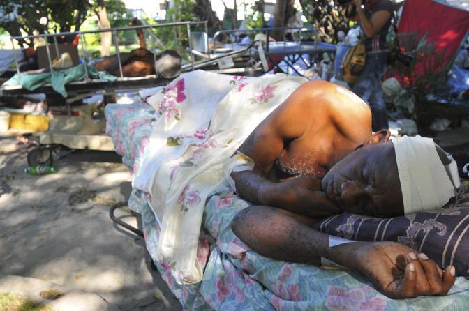 Un uomo riposa in un ricovero di fortuna (Epa)