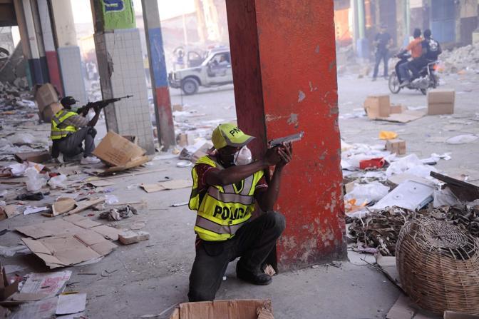 Poliziotti puntano le armi contro alcuni saccheggiatori in boulevard Jean Jacques Dessalines a Port au Prince (Epa)