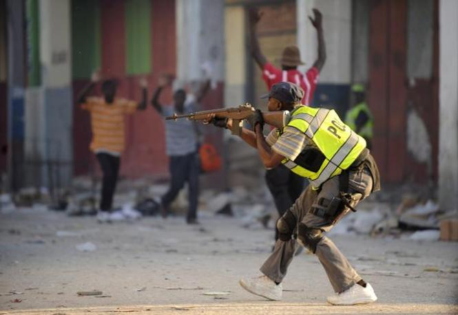 Un agente della polizia haitiana punta il fucile contro alcuni saccheggiatori (Epa)