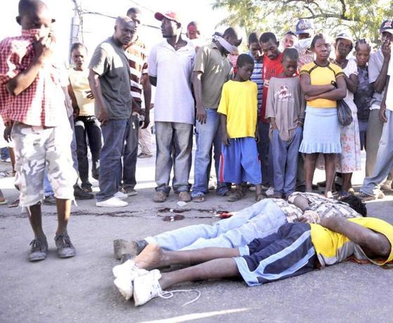 La folla guarda due uomini, sorpresi a rubare, che sono stati legati e fucilati in Delmas Road a Port au Prince. L'uomo con la camicia gialla era ancora vivo dopo essere stato colpito ma né la polizia né la gente ha cercato di salvarlo. (Epa)