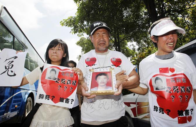 I familiari di un dipendente che si è suicidato, Ma Xiangqian, manifestano davanti allo stabilimento (Ap)