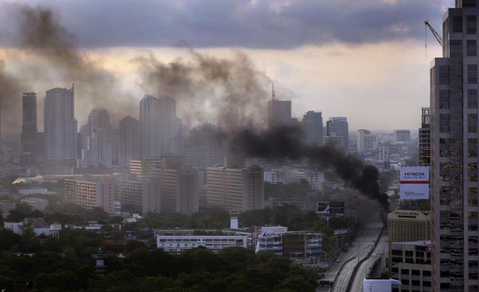 Bangkok, 15 maggio: gli scontri tra militari e camicie rosse vanno avanti ormai da tre giorni. Il cielo della città è oscurato dal fumo degli pneumatici incendiati dai manifestanti (Ap)