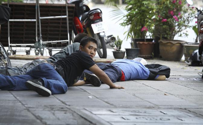 Tre uomini cercano di recuperare il corpo di un compagno caduto sotto il fuoco dei cecchini (Ap)