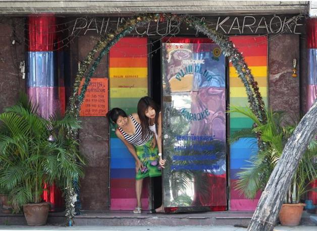 Due ragazze che lavorano in un bar karaoke si affacciano spaventate (Epa)