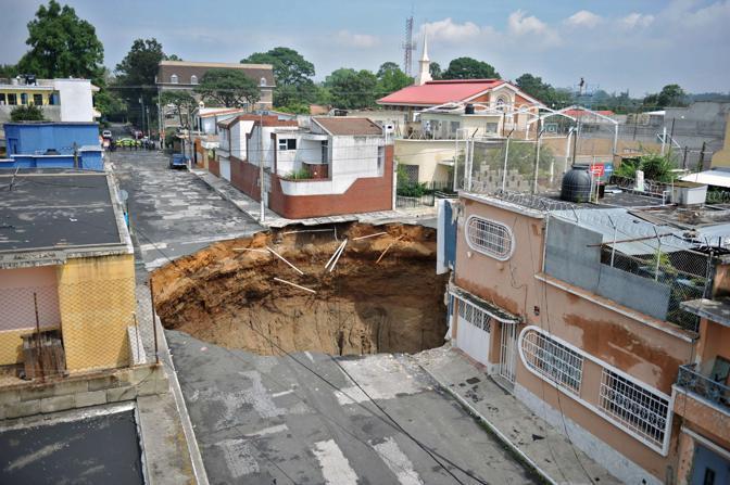 L'impressionante voragine al centro di una strada provocata dalla tempesta Agatha a Città del Guatemala (Afp)