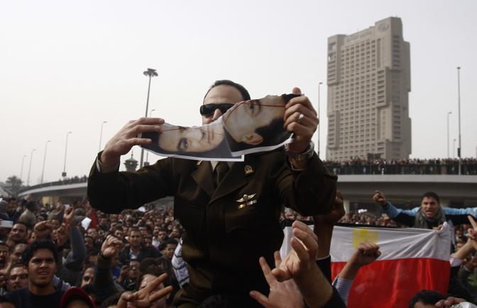 Un manifestante strappa un ritratto di Mubarak (Ap)