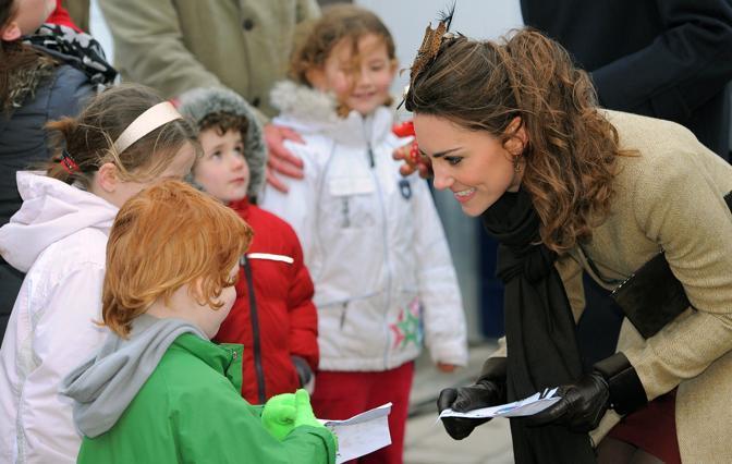 Kate indossava un cappottino beige, guanti in pelle, degli stivali a tacco alto e uno sfizioso copricapo di piume (Afp)