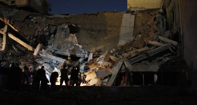 Il bombardamento delle forze della coalizione sulla sede del leader libico Gheddafi a Tripoli ha distrutto uno degli edifici del compound (Afp)