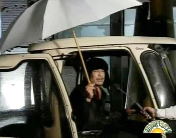 Tutti gli stili di Muammar Gheddafi: nella foto in alto la prima brevissima apparizione del leader libico durante le proteste. Grande ombrello bianco e colbacco stile pioniere dell'aviazione (Milestone)