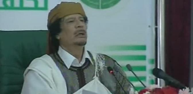 L'ultima apparizione di Gheddafi: volto scoperto, molto più rilassato, copricapo marrone e una djellaba a righe bianche e nere, con camicia e mantello di un candidissimo bianco (Ansa)