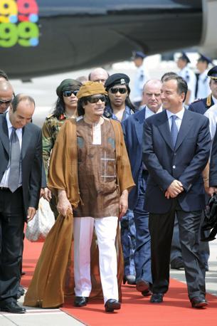Augusto 2010: il Raìs a Roma con Frattini indossa un mantello color sabbia e pantaloni bianchi (Photomasi)