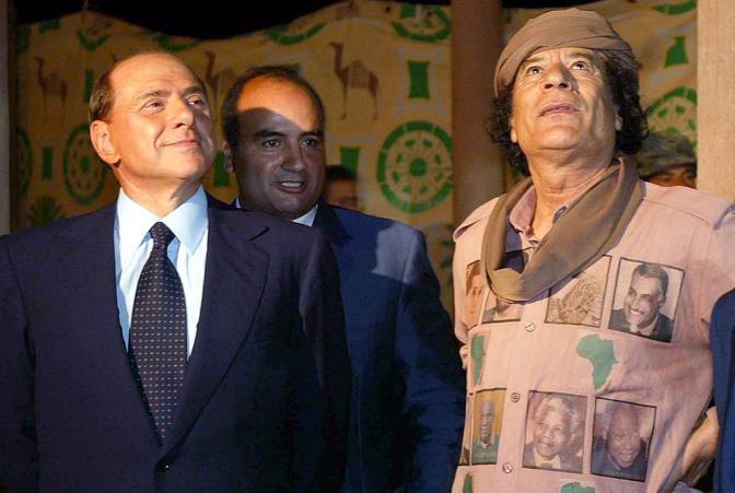 Il Colonnello col premier Silvio berlusconi in una foto del 2004. Sulla divisa di Gheddafi i volti di  Mandela e di tutti gli eroi dell' orgoglio africano  (Ansa)
