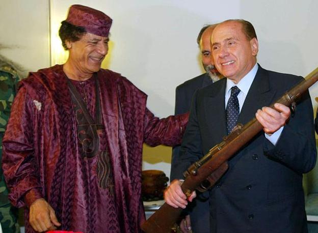 Ottobre 2002: Gheddafi in abito beduino color prugna con Berlusconi (Ansa)