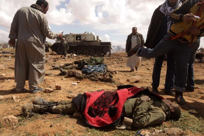 I tank centrati dai missili alleati nella zona di Bengasi. Uno dei ribelli scaglia un calcio alla testa del giovanissimo mercenario centrafricano morto nel bombardamento ad al-Wayfiyah, 35 km ad ovest della roccaforte antigovernativa (Afp)