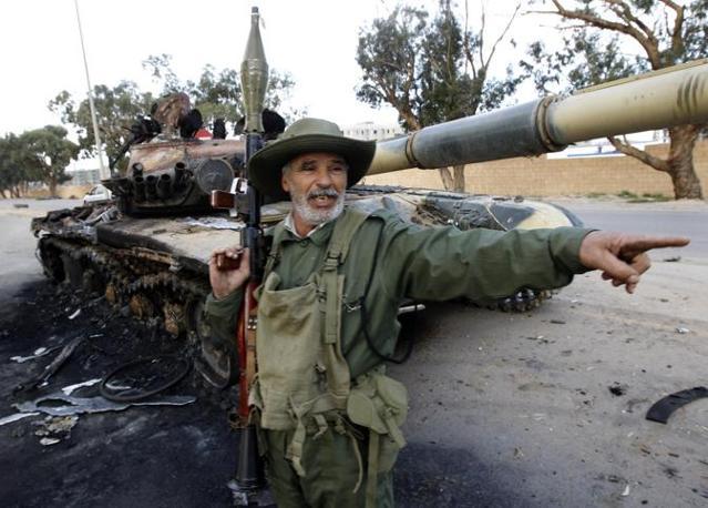 Un anziano ribelle con in braccio un lanciamissile festeggia la distruzione di un tank delle truppe governative alle porte di Gheddafi (Reuters)