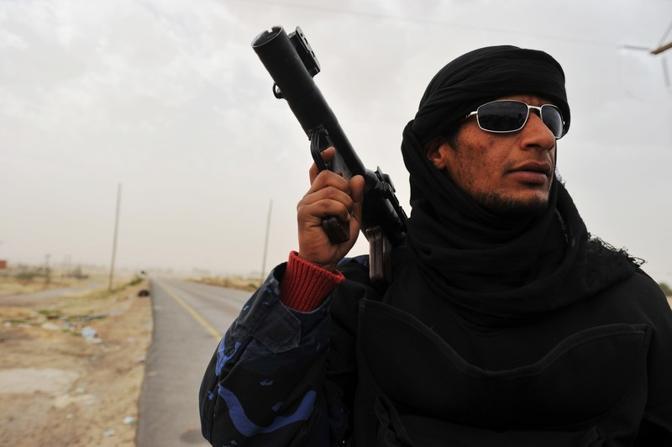Un oppositore con un copripaco usato dai beduini nel deserto