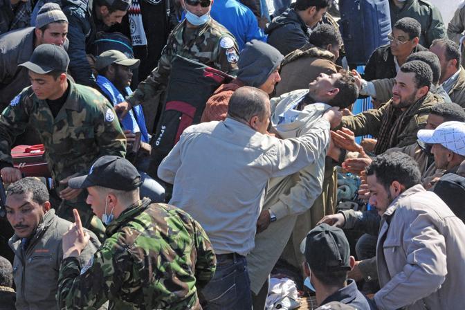 In fila per il cibo al confine tra la Libia e la Tunisia. Migliaia di profughi dalla Libia si sono ammassati al confine per cercare di entrare in territorio tunisino (Ansa)