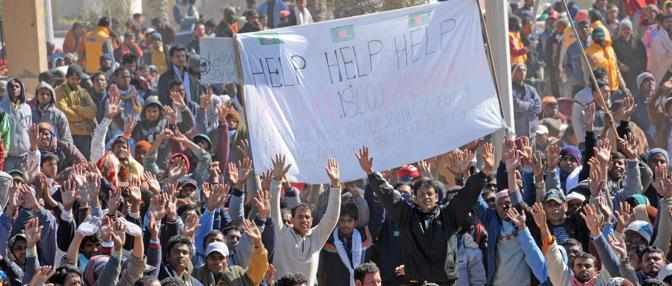 Cittadini del Bangladesh bloccati alla frontiera tra la Libia e la Tunisia espongono un telo con la richiesta di aiuto al loro governo (Ansa)