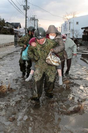 I soccorritori portano in salvo un anziano a Natori (Epa)