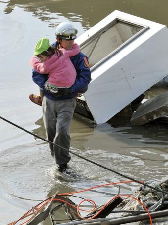 Un soccorritore porta in salvo una bambina a Kesennuma (Reuters)