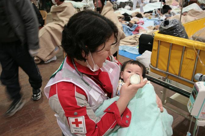 Un'infermiera dà il biberon a un bambino nel centro operativo della Croce Rossa per la prefettura di Miyagi (Reuters)