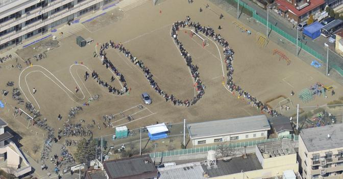 La coda per l'acqua nel campo sportivo di una scuola a Sendai (Reuters)