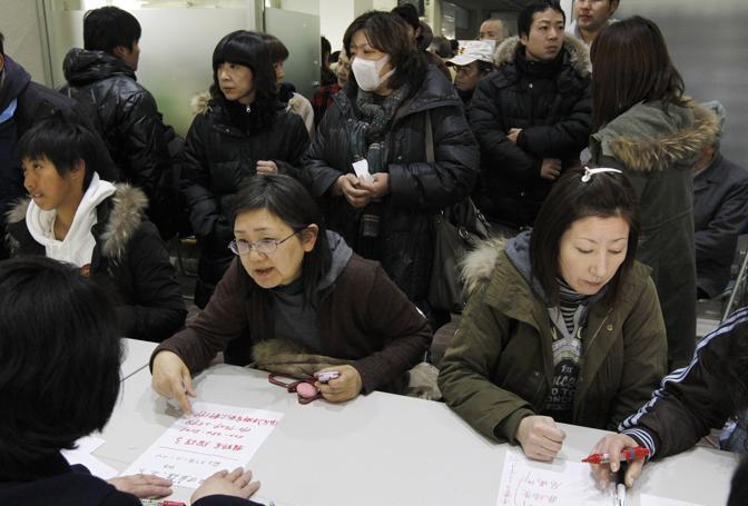 La coda per aver notizie dei familiari dispersi a Sendai (Reuters)