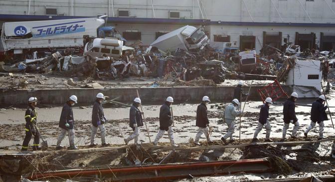 Si cercano superstiti nel mare di fango a Sendai (Reuters)