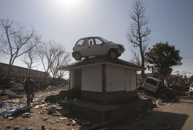 Un'auto sollevata dal maremoto a Sendai (Ap)