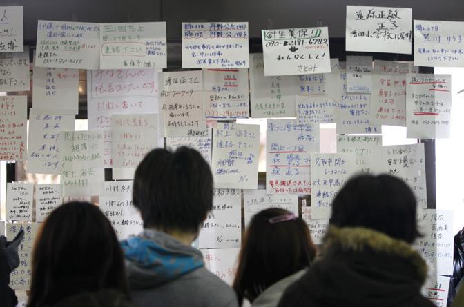 Bacheca con gli annunci per rintracciare i dispersi a Sendai (Reuters)