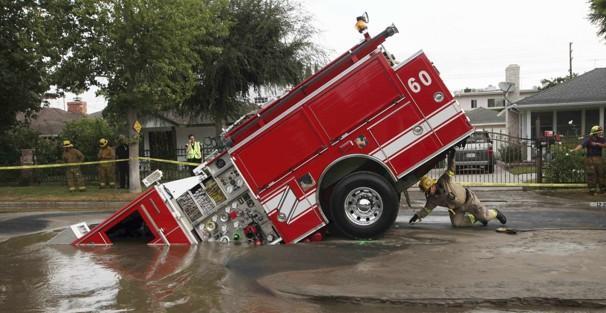Un camion dei pompieri di Los Angeles, bloccato da un buco apertosi in strada