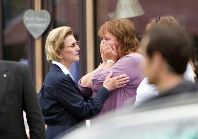La regina Sonja conforta una sopravvissuta alla strage compiuta da Anders Behring Breivik (Epa)