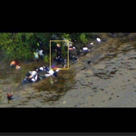 L'uomo sembra essere armato e sembra guardare verso un'altra persona ancora viva, un giovane che ha trovato riparo in acqua e che tiene il braccio alzato come in un gesto di implorazione