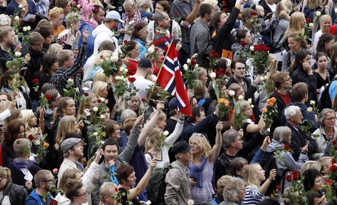 Migliaia di persone marciano impugnando delle rose, simbolo del partito laburista