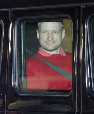 Il sorriso inquietante di Anders Behring Breivik, a bordo dell'auto che lo porta in tribunale (Olycom)