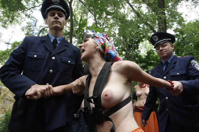 Poliziotti arrestano le attiviste del gruppo ucraino Femen durante una protesta contro il governo davanti alla sede dei ministeri di Kiev. L'Ucraina celebra oggi i 20 anni della separazione della URSS con cerimonie caratterizzate da un' ombra di tristezza per le aspettative non realizzate e le tensioni dopo l'arresto della leader dell'opposizione Yulia Tymoshenko. (Vladimir Sindeyev/Afp)