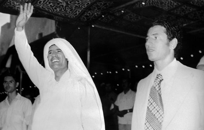 Giugno 1975: saluta la folla  a Tripoli. Al suo fianco Jalloud numero due del regime (Afp)