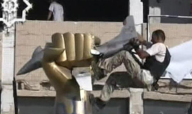 Un fermo immagine tratto da un video di SkyNews che mostra un ribelle che da la scalata alla statua voluta da Gheddafi all interno del compound dopo i raid aerei ordinati da Ronald Reagan su Tripoli e Bengasi del 1986. La statua raffigura un pugno chiuso dorato che accartoccia un caccia F-16 americano (Ansa)