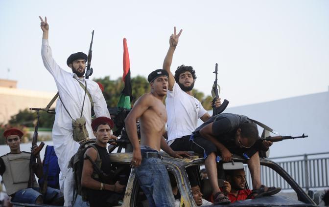 Ribelli libici in festa dopo aver espugnato il compound fortificato di Bab al-Azizya di Gheddafi a Tripoli (Afp/Filippo Monforte)