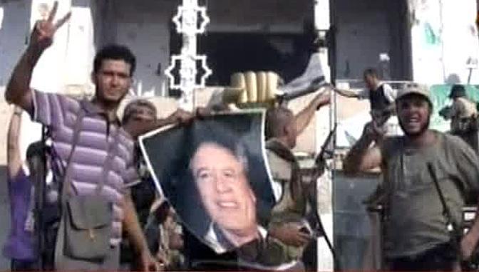 Un fermo immagine tratto da un video di Sky Tg 24 che ritrae alcuni ribelli libici entrati nel compound di Muammar Gheddafi a Bab al Aziziya che dopo aver decapitato un monumento del rais ne hanno calpestato la testa per mostrarla alle telecamere delle emittenti straniere entrate nella residenza-bunker del rais 23 agosto 2011 Sullo sfondo la statua voluta da Gheddafi all interno del compound dopo i raid aerei ordinati da Ronald Reagan su Tripoli e Bengasi del 1986 che raffigura un pugno chiuso dorato mentre accartoccia un caccia F-16 americano (Ansa)