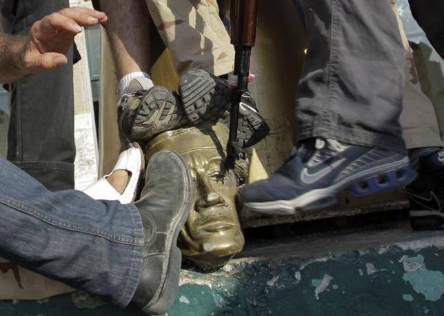 I ribelli calpestano una statua con l'immagine di Gheddafi presa nella sua fortezza espugnata (AP Photo/Sergey Ponomarev)
