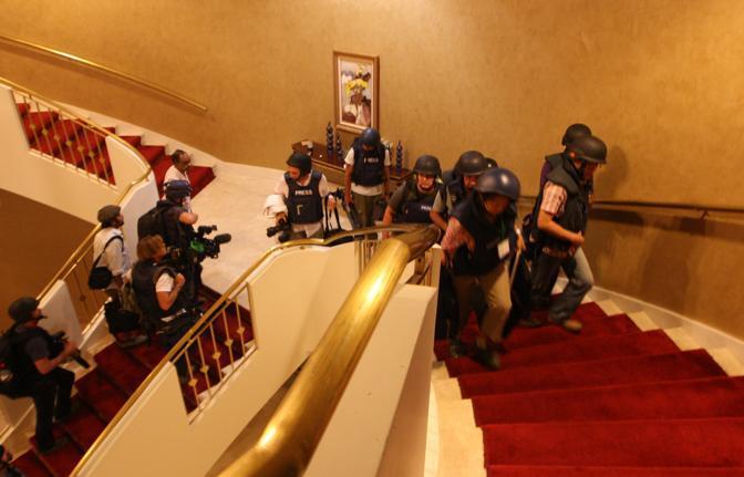 Gli inviati sono stati  costretti a scappare per le scale, salendo di piano in piano, per sfuggire ai proiettili delle truppe pro Gheddafi che pattugliano la hall dell'albergo, con il timore di essere usati come ostaggi (Ap)