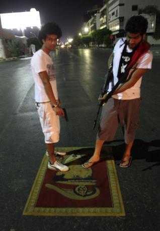 Calpestata una immagine di Gheddafi a Tripoli (Afp)