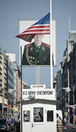 Berlino, una bandiera americana a mezz'asta al Checkpoint Charlie davanti al ritratto di un soldato russo (Afp)
