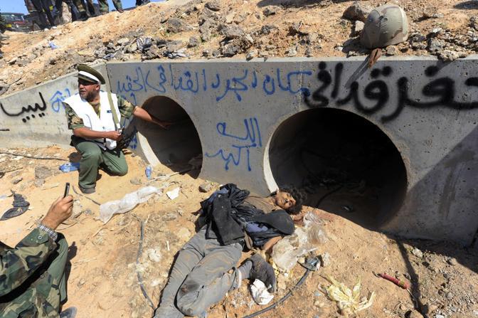 I condotti in cui si erano asserragliati Gheddafi e i figli prima di essere catturati. All'esterno uno dei suoi fedelissimi giace senza vita (Afp)