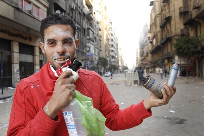 Un ragazzo con in mano le bombolette di gas sparate dalle forze di sicurezza (Lapresse)