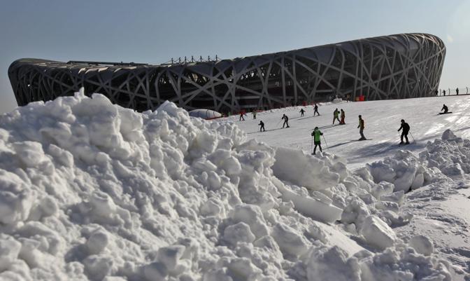 A Pechino il famoso stadio a forma di nido d'uccello costruito per le Olimpiadi del 2008 è stato trasformato in un maxi parco sciistico grazie all'innevamento artificiale. Sono migliaia i cinesi che ogni giorno si cimentano con tavole, slitte e ogni mezzo (Epa/Young)