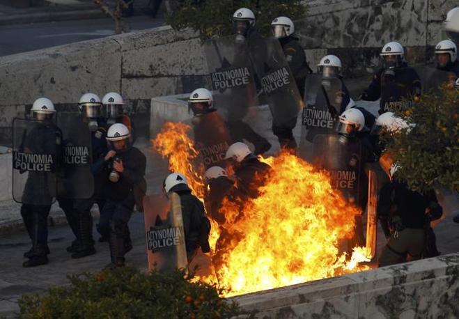 Gli agenti in assetto anti-sommossa fronteggiano i black bloc all'ingresso del Parlamento (Reuters/Yannis Behrakis)