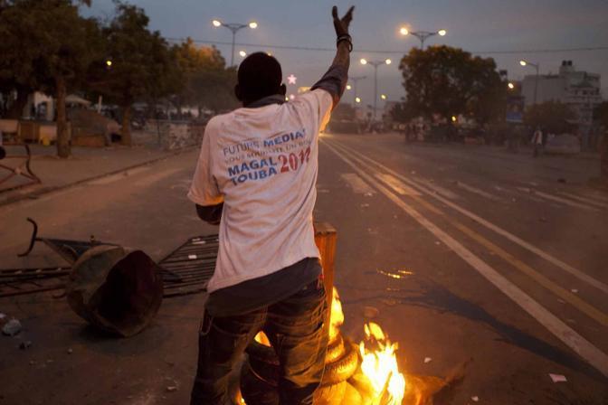 La protesta infiamma a Dakar dove la strada che porta al palazzo presidenziale è stata teatro di roghi di copertoni (La Presse)